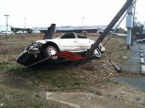 Damaged Car on Top of Pole