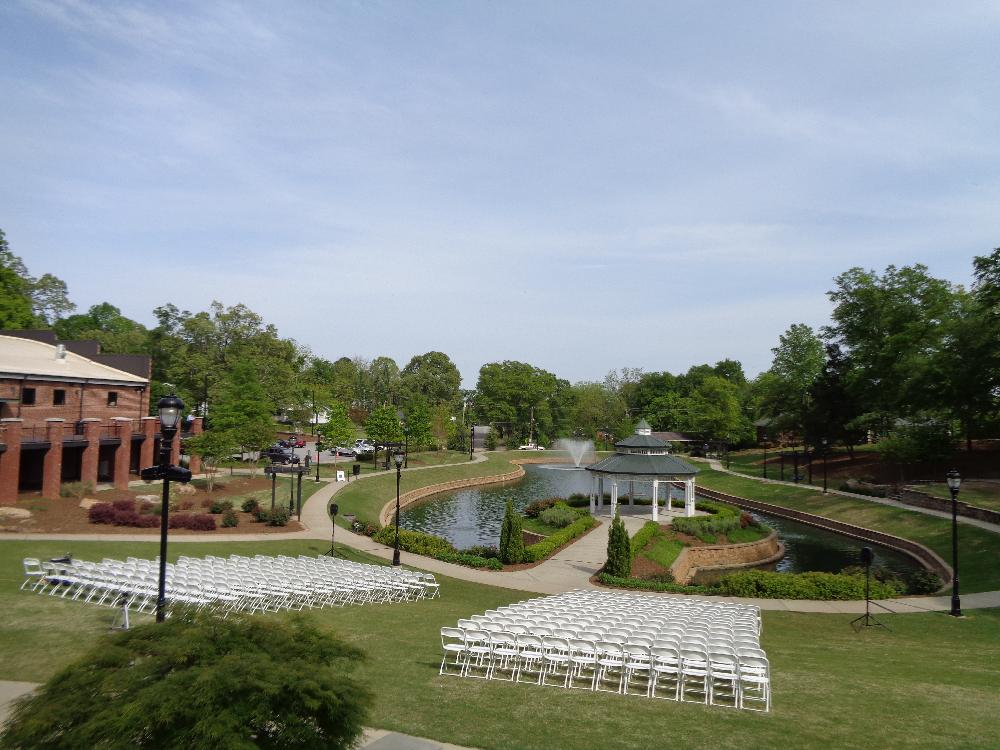 Rows of White Chairs Facing a Scenic Gazebo by a Pond