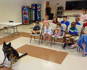 Kids in chairs looking at K-9