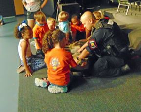 Young kids in a circle with Officer at Coast 2 Coast Daycare