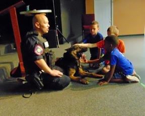 Kids petting K-9 by officer